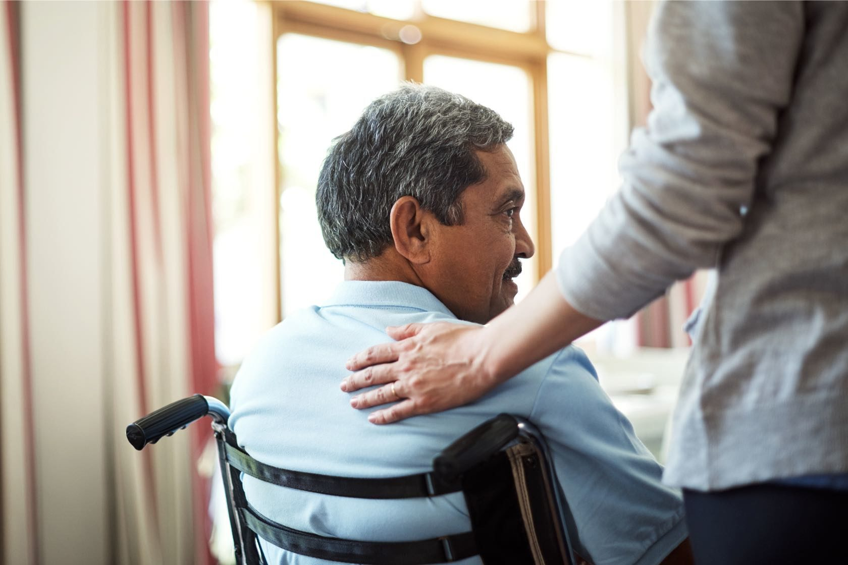 Man happily sitting in wheel-chair in Silver Birch assisted living senior community