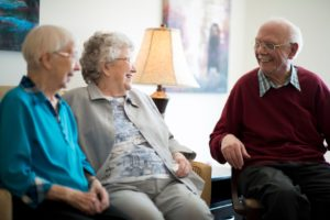 Seniors laughing together sitting down at assisted living community at Silver Birch
