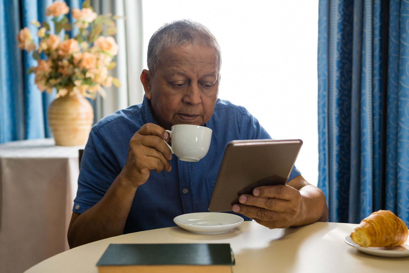 Elderly adult drinking a cup of coffee in assisted living at Silver Birch